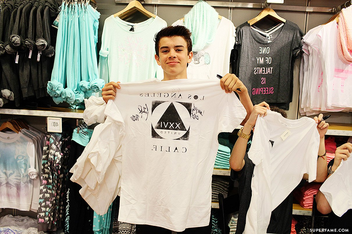 Hayes Grier holds t-shirt.