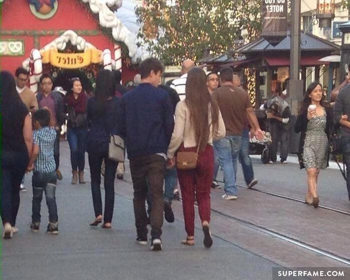 Cameron holding hands with Rachel.