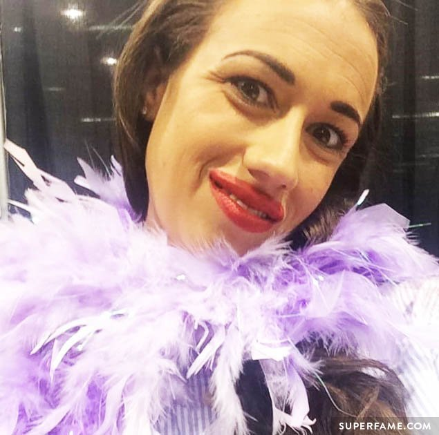 Miranda Sings dons purple feathers.