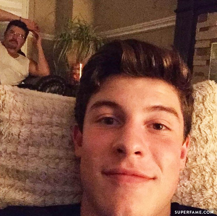 Shawn Mendes sitting on the sofa with dad.