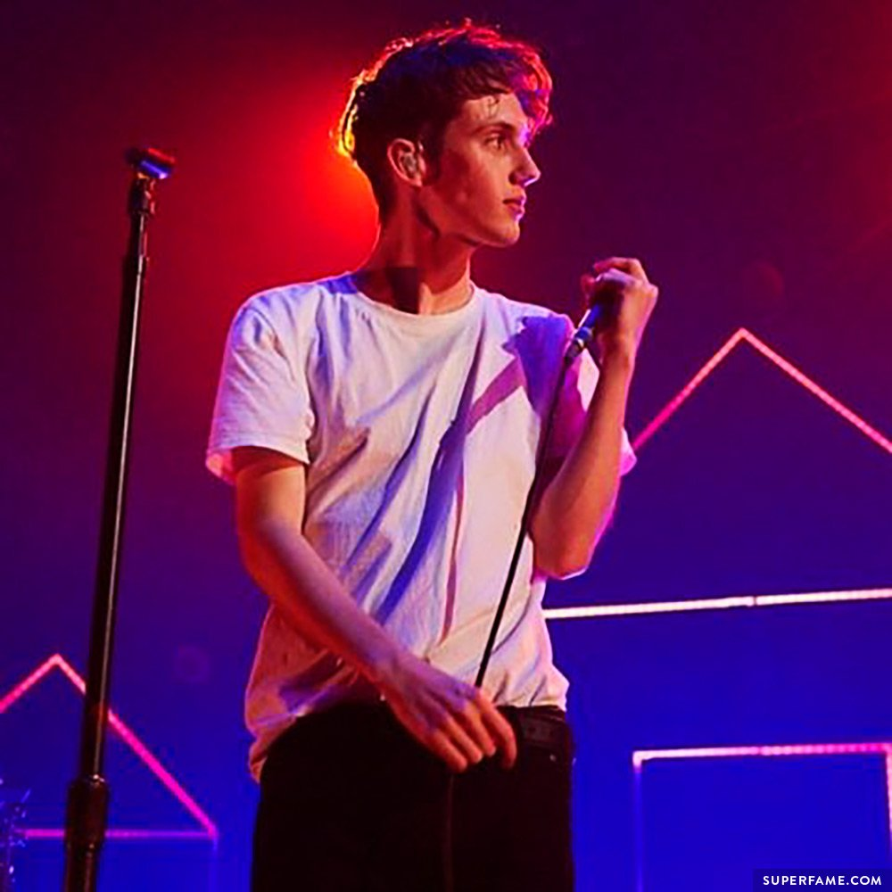Troye performs live in a white t-shirt.